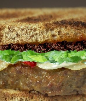 Italian meatloaf sandwich with tapenade and fresh spinach.